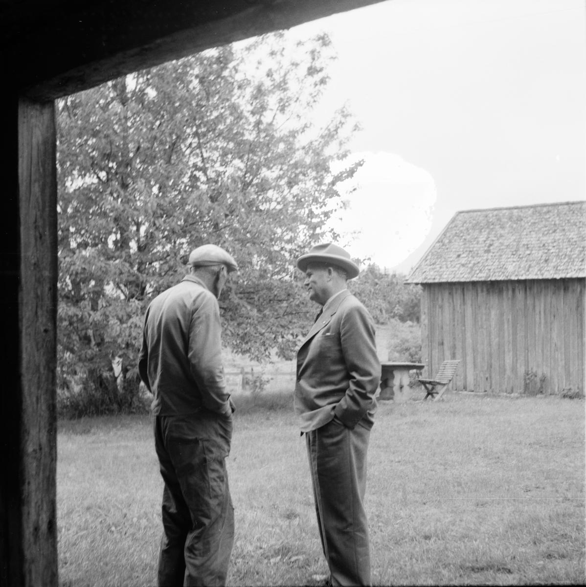 Två herrar på gårdplan..