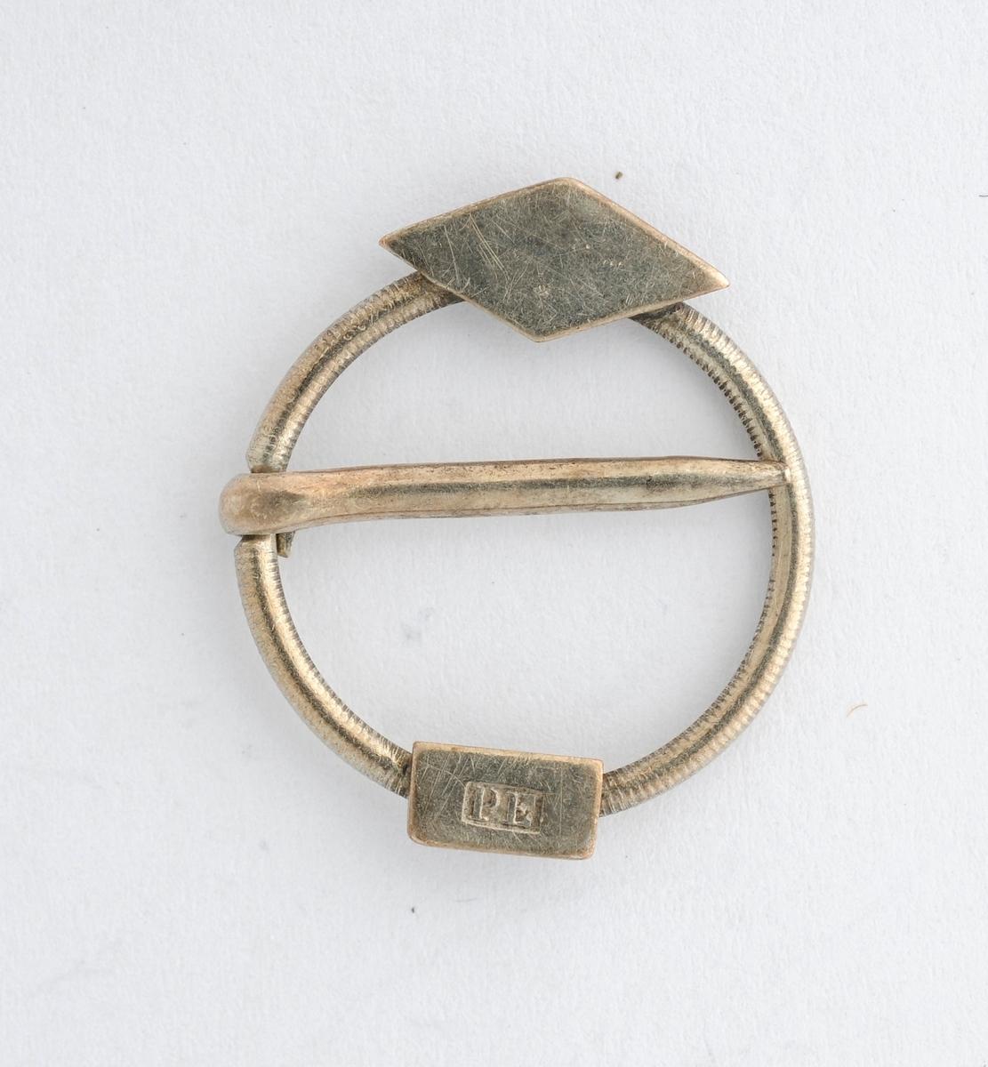 Barnesølje, sprette i sølv. Støypt ring, pålodda ei rombe liknande plate, og ei rektangulær plate med stempel P E på framsida.Laus tann.