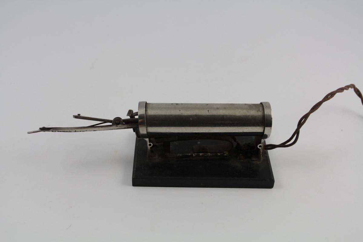 a) Krølltang består av to deler. Underdel som har vulstform, overdel rørformet og spent fast m/fjær til underdel.  b) Varmeelement på sokkel m/elektrisk kobling.