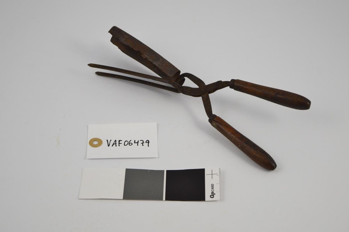 Krølltang med to håndtak i tre og to sylinderformede tinner, festet til en bølgeformet blikkplate som er tilpasset den andre armens tinner.