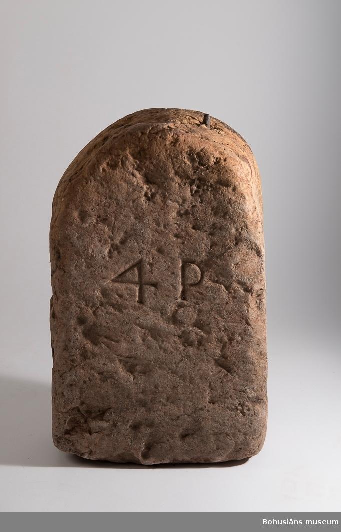 """Föremålet visas i basutställningen Uddevalla genom tiderna, Bohusläns museum, Uddevalla.  Stenvikt av röd kalksten med inristade tecknen: 4 P  """"Om Uddevalla fick stapelrätt vore det  slut med  Göteborg - - - Särskilt skar det sig i fråga om järnet. Det insinuerades, att det gick så primitivt (och ohederligt) till i Uddevalla, att man där hade stenar i stället för justerade vikter. På Uddevalla museum finnes verkligen en i Bäveån påträffad stenvikt 4 pund, som möjligen kan ha avsetts härmed.""""  ur Kristiansson, S.: Uddevalla stads historia del I.  Ur Svenska Akademiens Ordbok: Lödigar, viktlödjer, lodja 1794--1804. lödja (-di-) 1625, lödigar, av  lode, loie, blystycke, sänke, viktlod; jfr holl. loodje, metallstycke av viss vikt, användt vid vägning, viktlod; särsk. om (i sht vid järnhanteringen använda) tunga viktlod av gjutjärn.   Ur handskrivna katalogen 1957-1958: Stenvikt """"4 P"""", röd kalksten. H. 42,5; L. 27; Br. 15cm; rundad överdel, handtaget sönderrostat, endast stumpar kvar; f.ö. hel.  Lappkatalog: 39  Ur handskriven katalog över Uddevalla Musei Historiska Samlingar, svenska avdelningen, yngre föremål upprättad  år 1916 av intendent Knut Adrian Andersson: I:70:13 """"No 13. Stenvikt s.k. Stenlädja (42 x 25 x 15 cm.) Funnen på botten av Bäve-ån, där Kålgårdsbergsgatan utmynnar i norra Hamngatan mitt för den äldsta fiskförsäljningsplatsen i Uddevalla. Vikten var vid uppfiskandet försedd med förrostat handtag, vilket snart föll sönder. Skänktes 8/6 1896 av Grosshandlaren Ad. P. Zachau. Den väger 4 pund = 34 kilo."""""""
