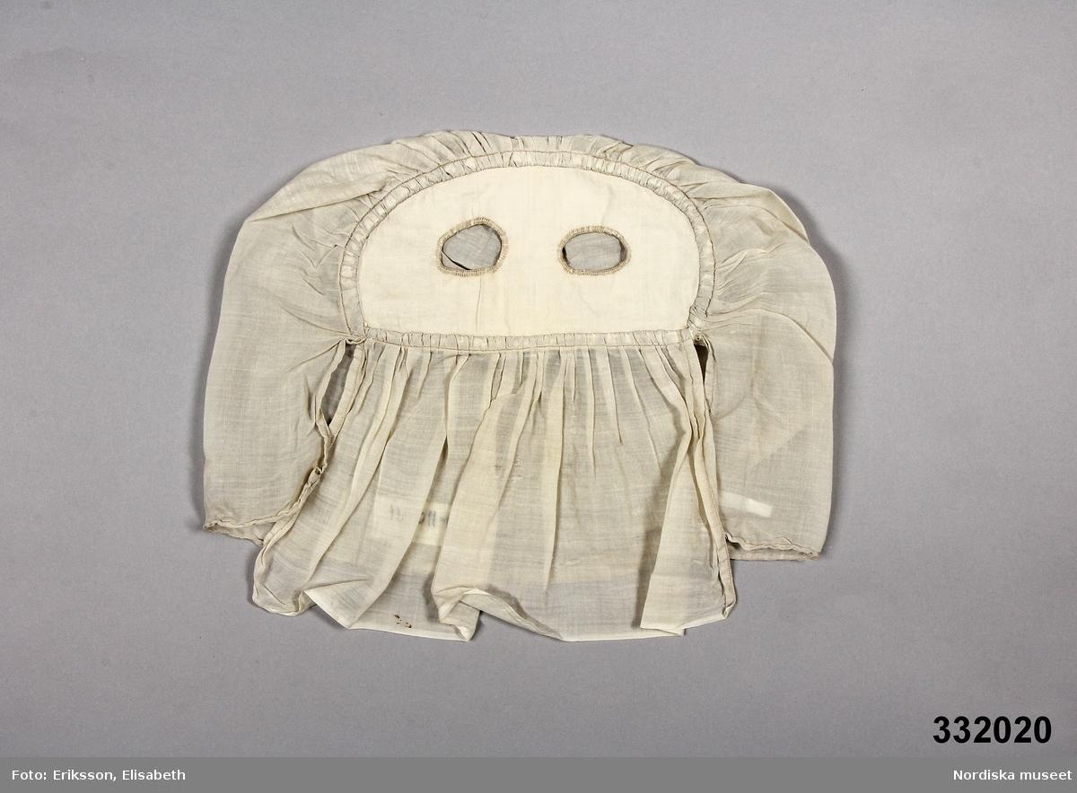 Tunn beige ansiktsmask av textil. Utformad som en huva med två hål för ögonen. Anm: Masken har några små fläckar. Märt med en textillapp med Kriminalvårdsstyrelsens nummer N-110091. /Johanna Skoglund 2013-04-22