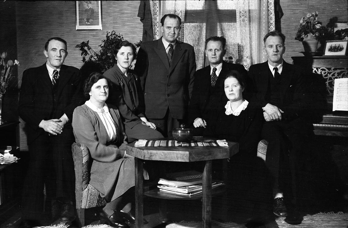 Gruppebilde som trolig viser Ole Kirkbak ( i midten bak) og hans søsken. Kirkbak, som var poståpner på Lena 1940-1949, var født i Ålen i Sør-Trøndelag, og iflg. folketellinga for 1941 hadde han seks søsken, hvorav to jenter, og det stemmer bra med bildet, uten at det kan tas som sikkert. Bildet er trolig tatt i tilknytning til Kirkbaks 50-års jubileum januar 1949.