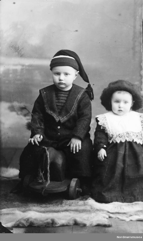 To barn, gutt og jente, trolig søsken. Gutten sitter på en trehest på hjul. Dei er med foreldra på SU-L91.0203 og 0248.