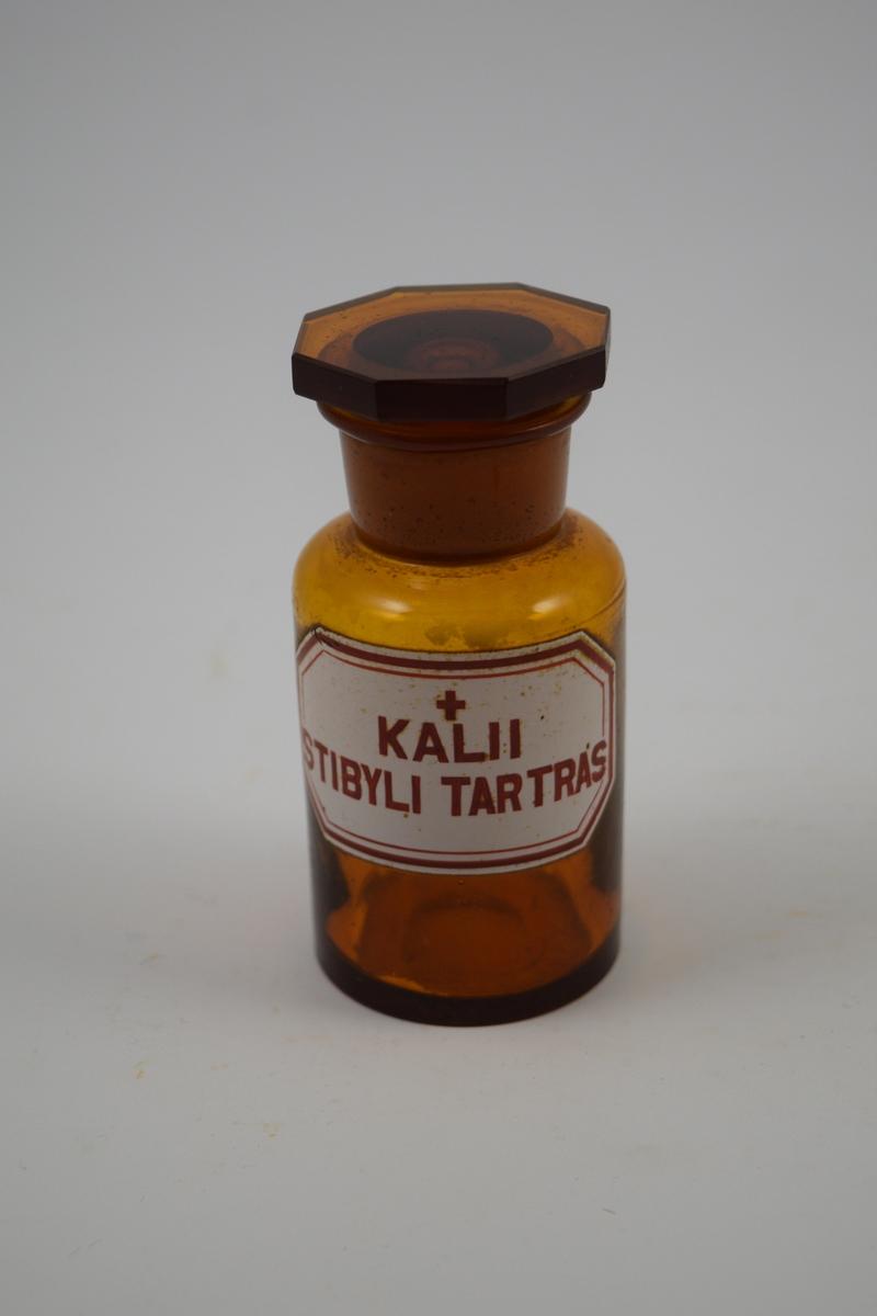 Brun glasskrukke med brun propp. Hvit etikett påsatt: rød skrift. Ett rødt kors - betyr at innholdet er giftig. Brukt til oppbevaring av pulver. Kalii Stibyli tartras ble brukt ved behandling av veneriske sykdommer/kjønnssykdommer.