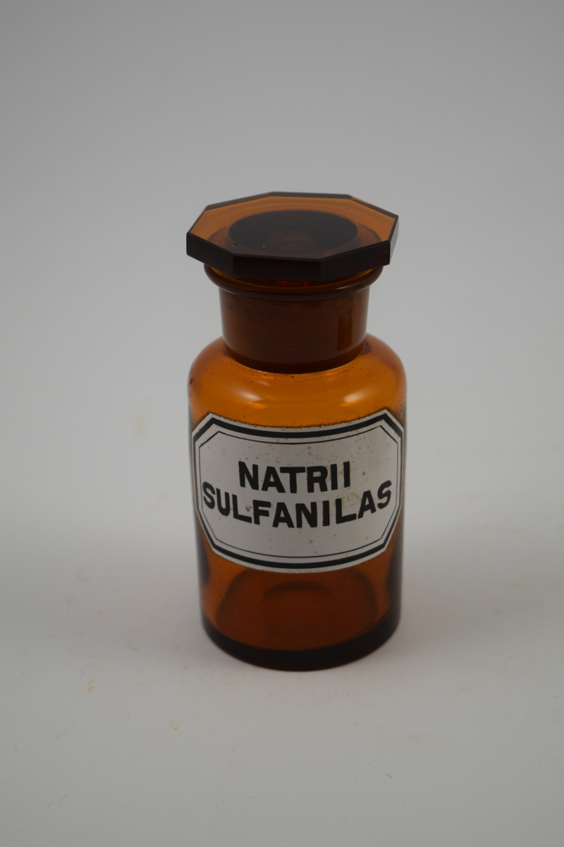 Brun glasskrukke med brun propp. Påført etikett, hvit med svart skrift. Har inneholdt Natrii sulfanilas, et sulfatpreparat - mot mikroorganismer.