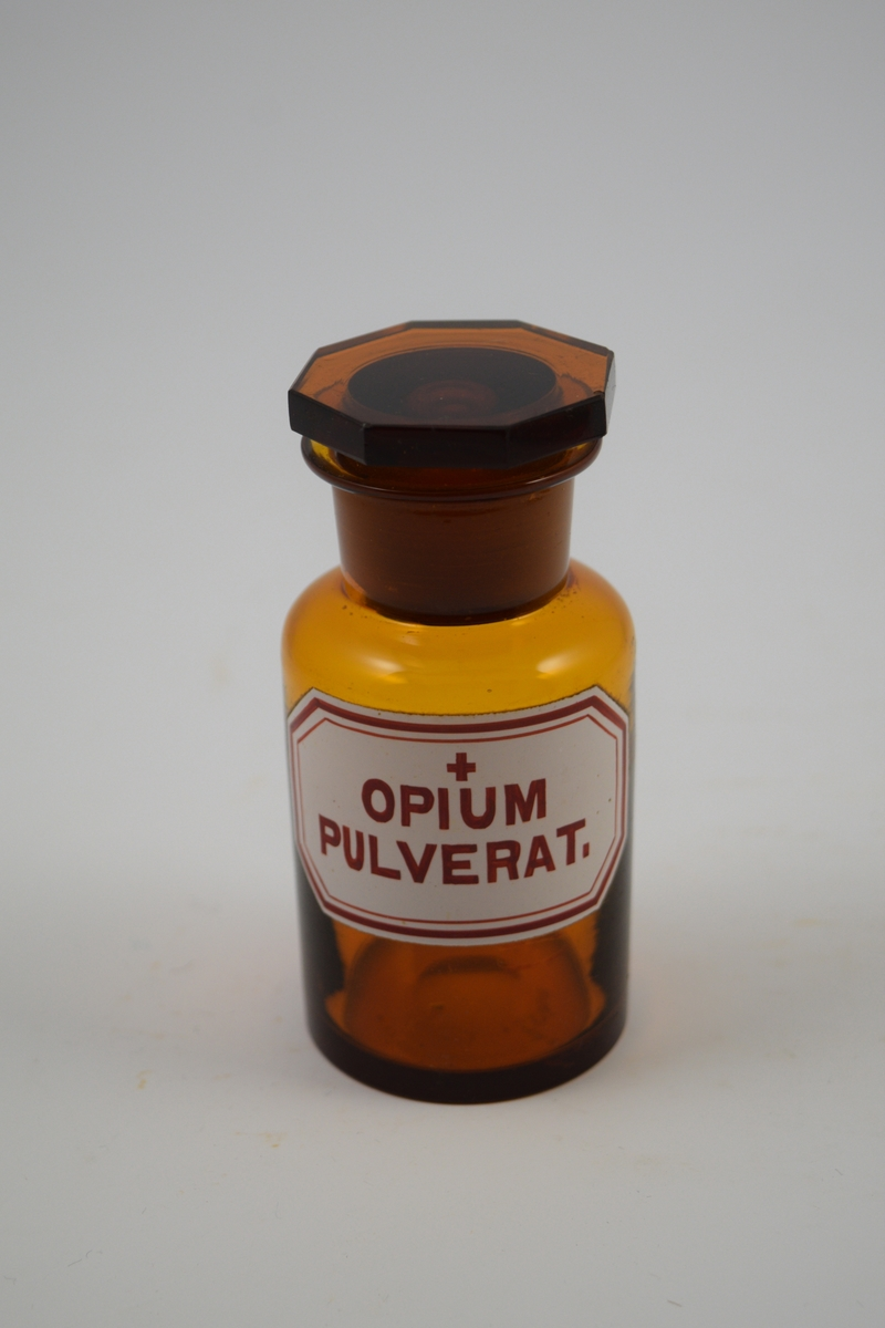 Brun glasskrukke med glasspropp. Etikett: hvit med rød skrift og ett kors - betyr at innholdet er giftig. Har inneholdt opiumspulver - brukt i smertestillende og hostestoppende.