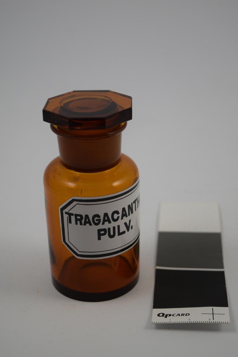 Brun glasskrukke med glasspropp. Hvit etikett med sort skrift. Trangacantha Pulv. brukes til tykningsmiddel, til festing av tannproteser.