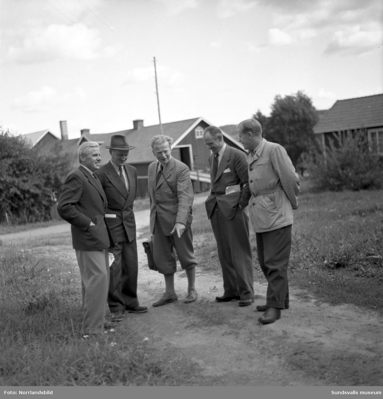 Jordbruksmöte i Kungsnäs. Fem herrar på en liten väg, ekonomibyggnader i bakgrunden.