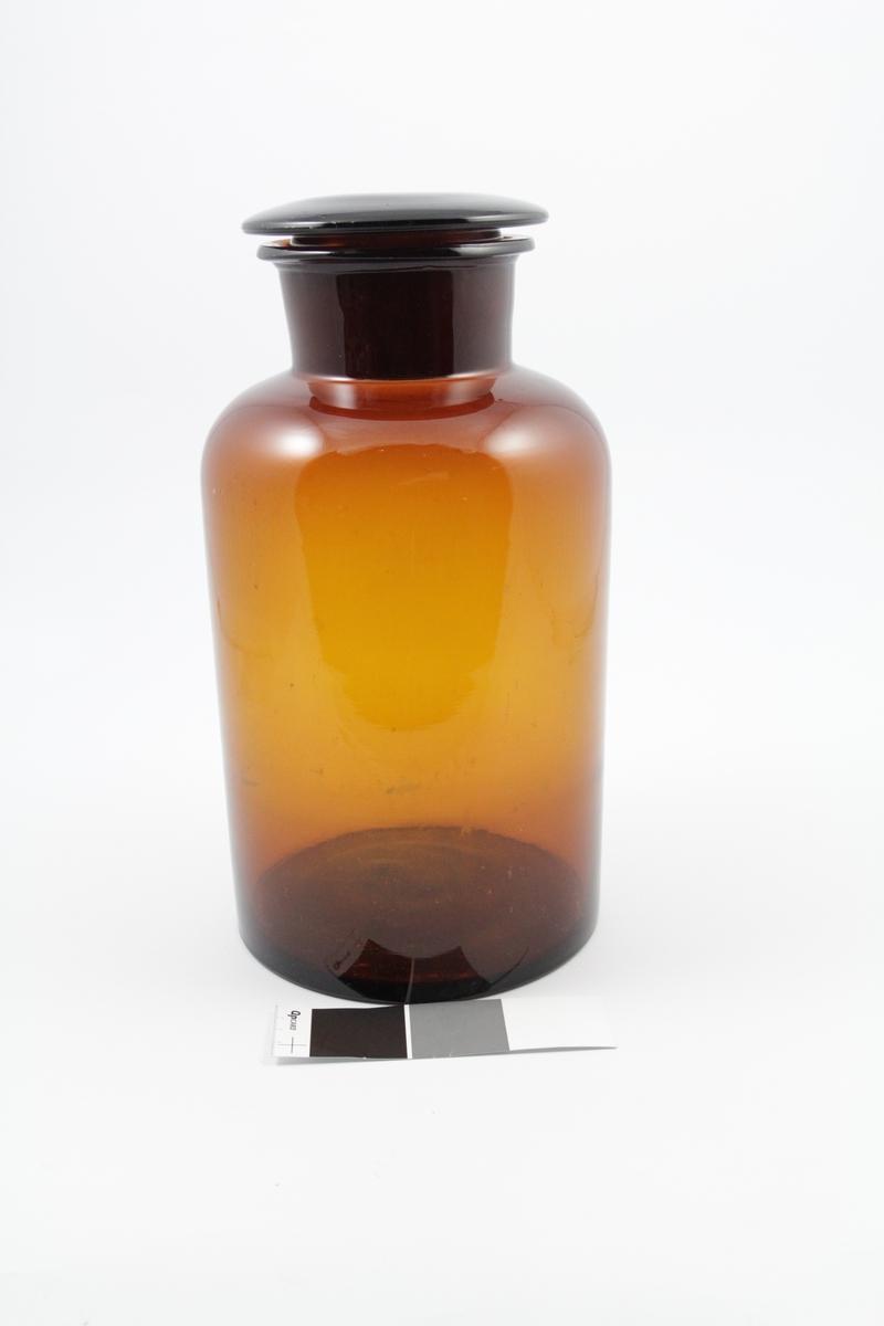Brun glasskrukke (standglass) med vid hals, glasspropp. Brukt til oppbevaring av pulver.