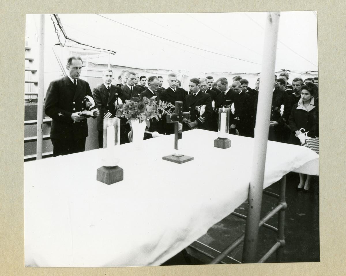 Bilden föreställer högbåtsman Grundströms minnesgudstjänst ombord på minfartyget Älvsnabben. På bilden syns ett altare med ljus, blommor och ett kors. Bakom altaret står besättningen klädda i mörka uniformer med huvudbonaderna under armarna medan prästen talar. Bilden är tagen under Älvsnabbens långresa 1966-1967.