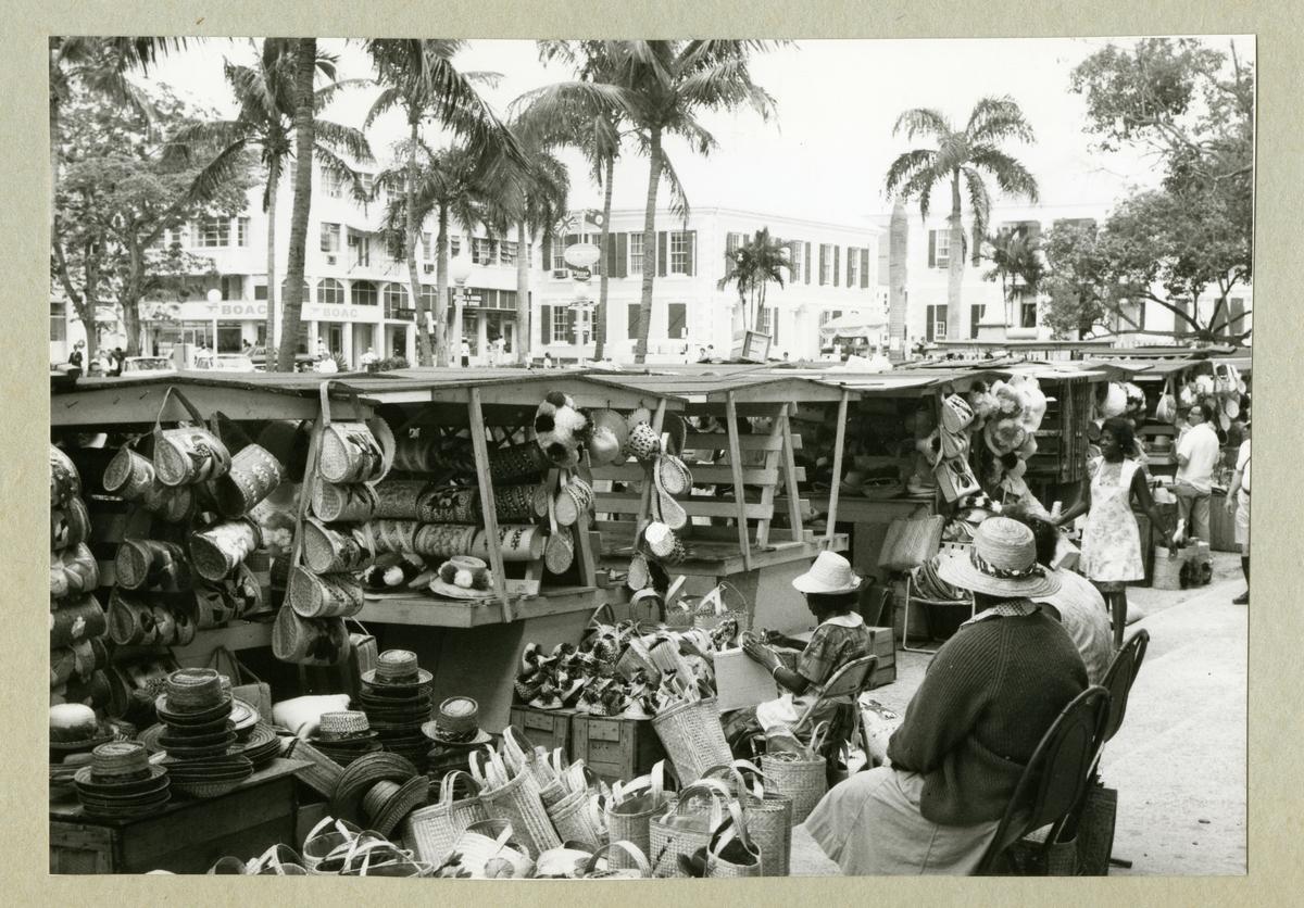 Bilden föreställer gatuförsäljning i Nassau. På bilden syns flera stånd med hattar och väskor. I bakgrunden syns palmer och bebyggelse längs med gatan. Bilden är tagen i samband med minfartyget Älvsnabbens långresa 1966-1967.