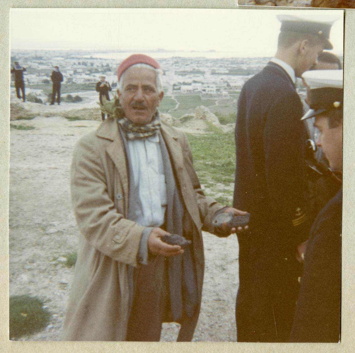 Bilden föreställer en man som visar två föremål för uniformsklädda män från Älvsnabbens besättning i Karthago under långresan 1966-1967.
