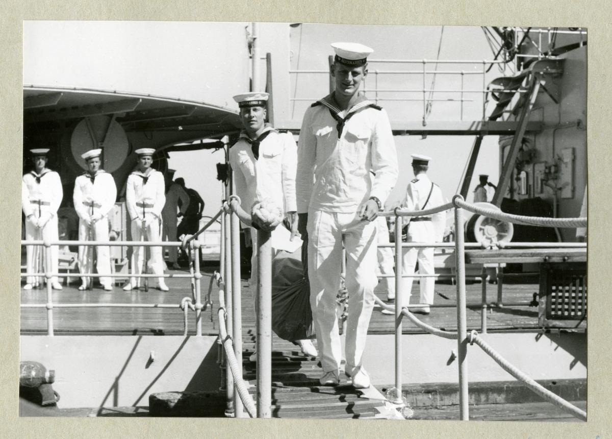 Bilden föreställer delar av den uniformsbeklädda besättningen ombord på minfartyget Älvsnabben, varav två är påväg över landgången. Bilden är tagen under fartygets långresa 1966-1967.