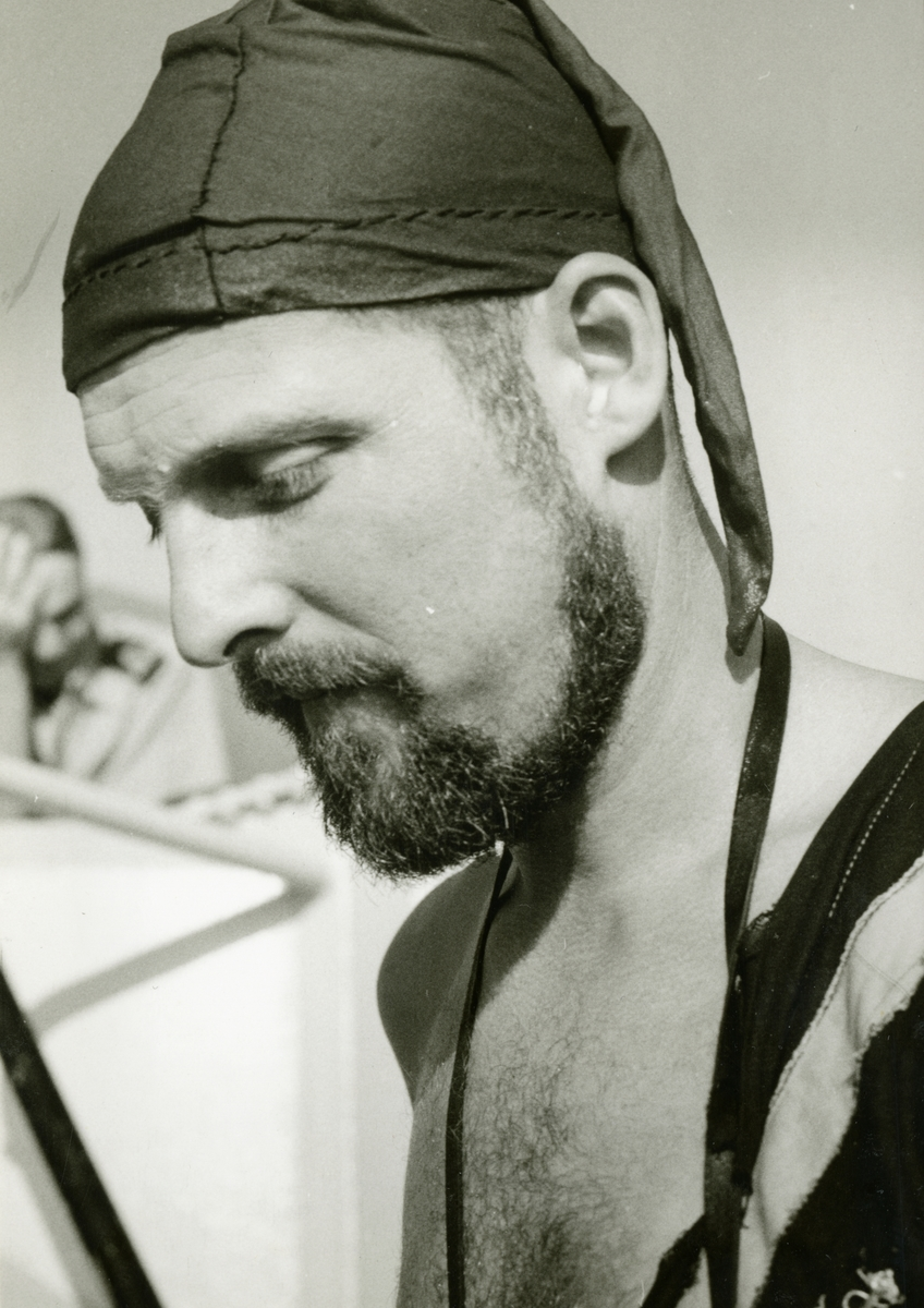 Bilden föreställer en skäggig man med en blöt luva på huvudet. Det är stridsledningsofficeren löjtnant Dag Lundman som fungerar som löparnisse under ett linjedop. Bilden är tagen i samband med ett linjedop ombord på minfartyget Älvsnabben under långresan 1966-1967.