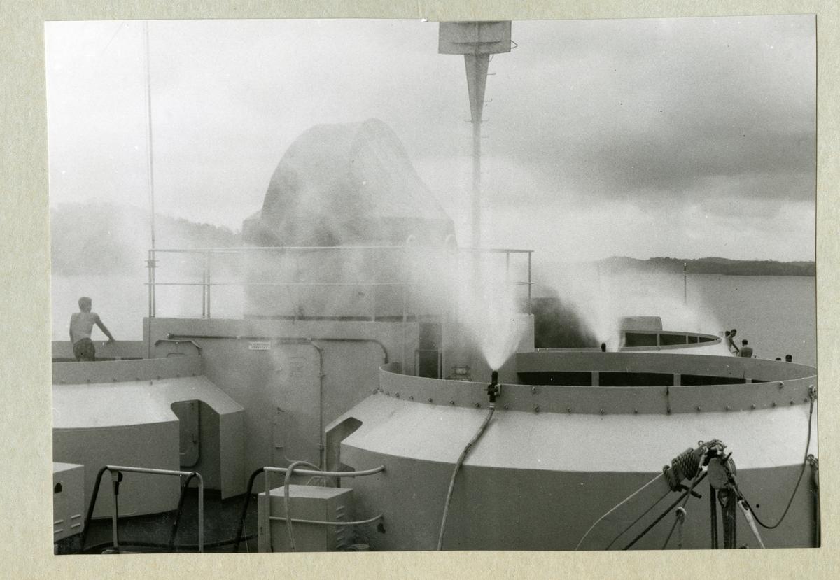 På bilden syns minfartyget Älvsnabbens förskepp med sprinklers på för att skölja däcket från saltet och minska korrosionsbenägenheten. Bilden är tagen på Gatunsjön i Panamakanalen under långresan 1966-1967.