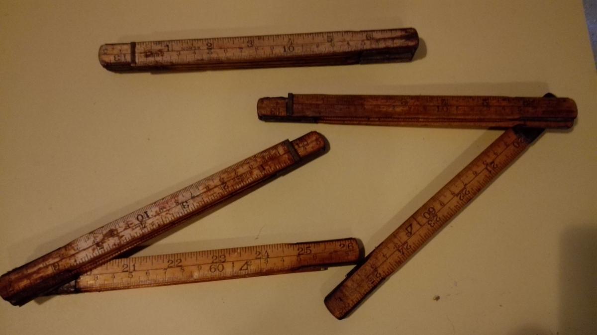 Tre samanleggbare tommestokk med seks ledd, Stokkane er 100 cm lange, og har mål både for centimeter og norske tommar. Dei to ytste ledda er kortare enn dei fire i midten.