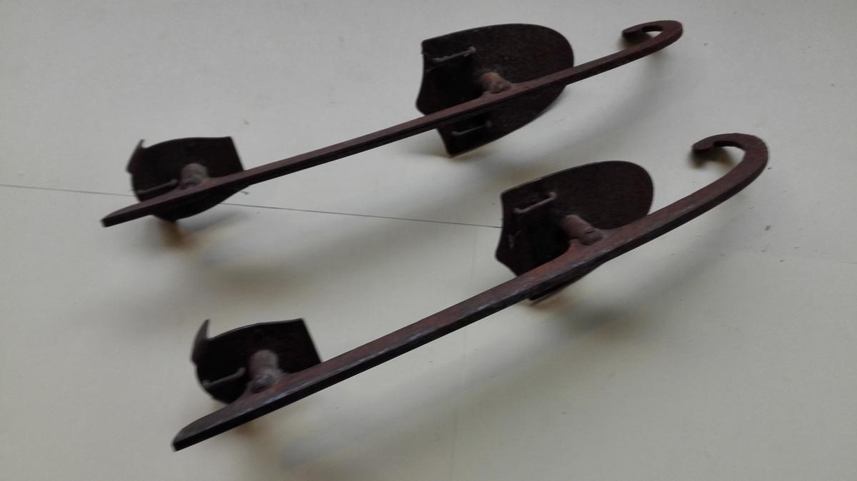 Skøyter med todelt fotplate. På kvar fotplate er to små piggar for p få skoen til  sitja stødig. Under er det hemper av jern til å tre gjennom reimar i. Skøytene er rusta.