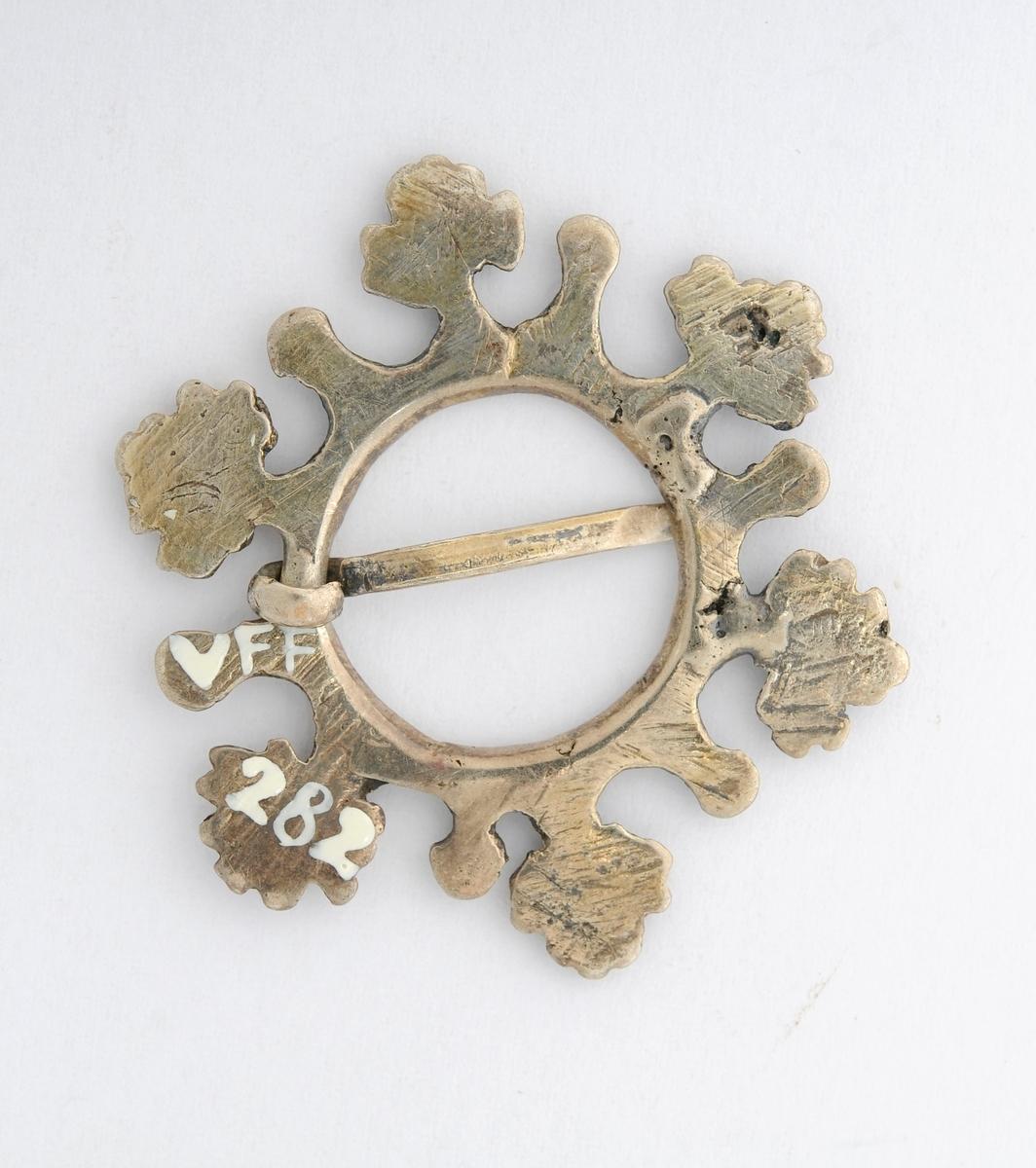 Sølje, spirsølje i sølv (utan stempel). Støypt med seks store taggar og seks små i ein ring. Open tann (nål). Bladdekor på framsida, baksida er glatt.