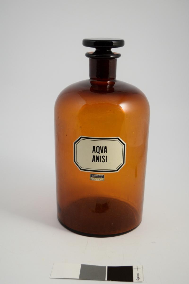 Brun glassflaske, smal hals, brun glasspropp. Påført hvit etikett med sort skrift. Flasken brukes til oppbevaring av løsninger. Anisvann ble brukt som smakstilsettning.