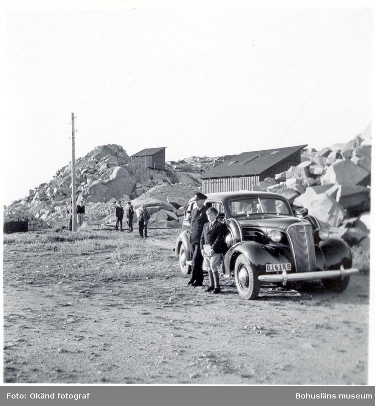 En man i uniform och en pojke står intill en bil parkerad vid stenhuggeriet i Rörvik