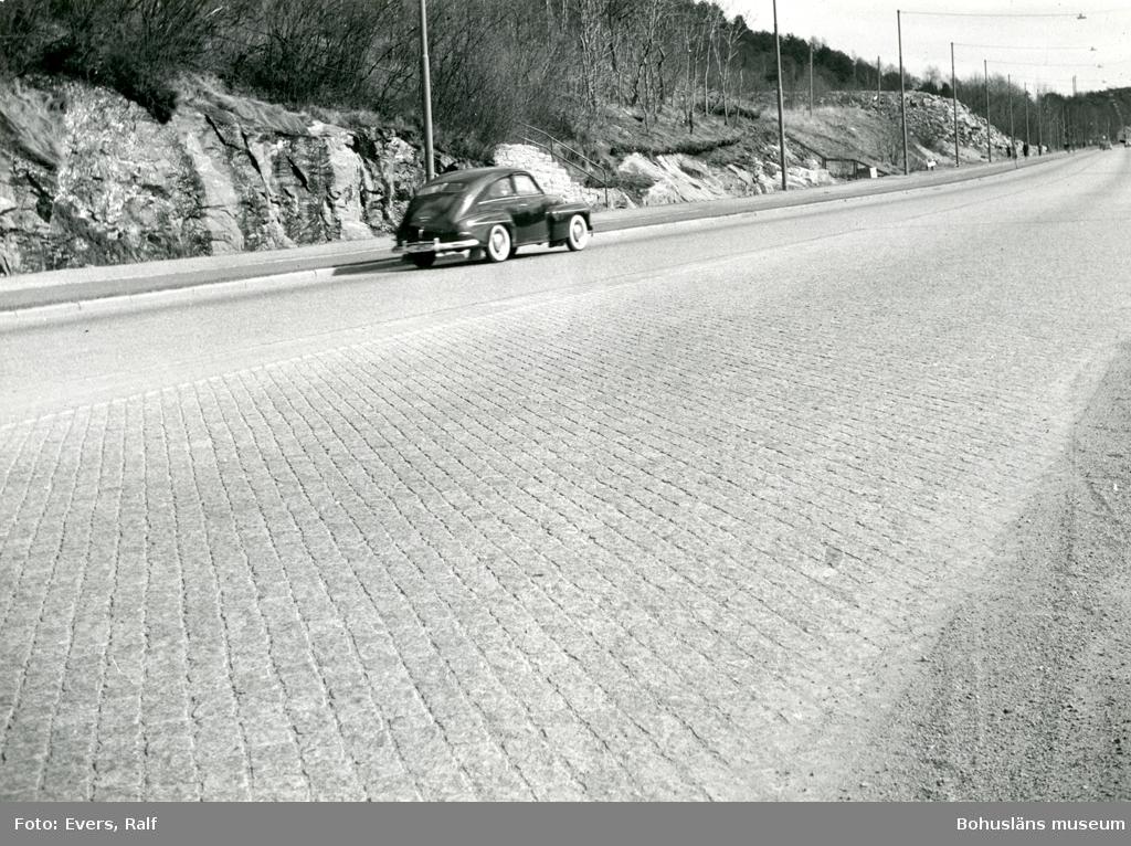 En bil åker längs en stenlagd gata