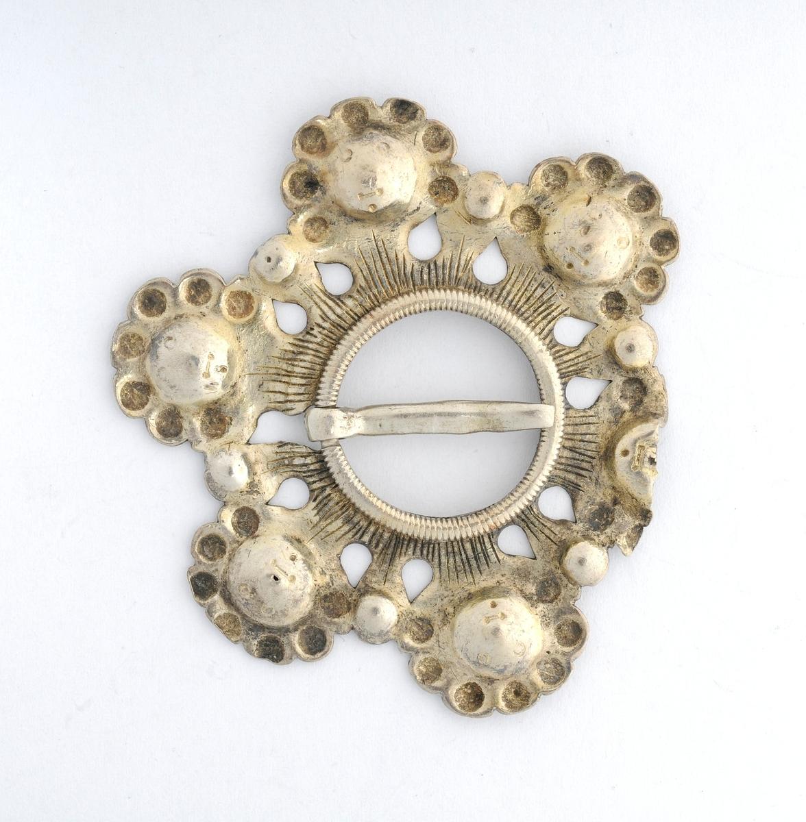 Sølje, i sølv (utan stempel).  Rund hamra plate med seks blad som er forma som eit ansikt. Open sirkel i midten med tann (nål). Tanna er avbroten. Det eine bladet er også avbrote.