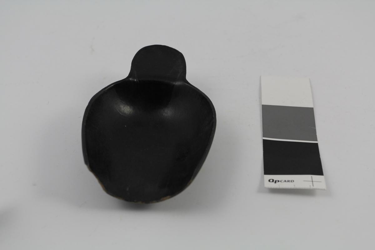 Skje i bakelitt, sort. Brukt til å øse pulver ved legemiddelproduksjon.