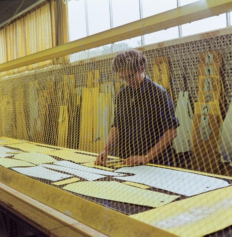 Ansatt i konfeksjonsfabrikken hos Jonas Øgænd Sandnes lager en skjæretegning med en fargemaskin.