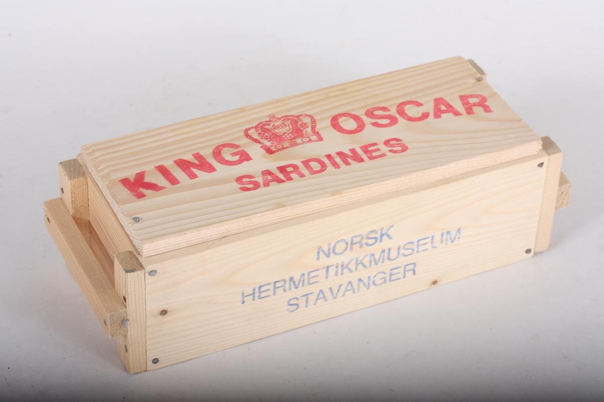 Lita trekasse med lok som er tilrettelagt for 6 sardinboksar. Salsartikkel ved Norsk Hermetikkmuseum i Stavanger.