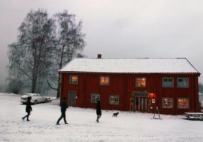 Et rødt, stort, gammelt trehus med lys i vinduene og snø omkring.