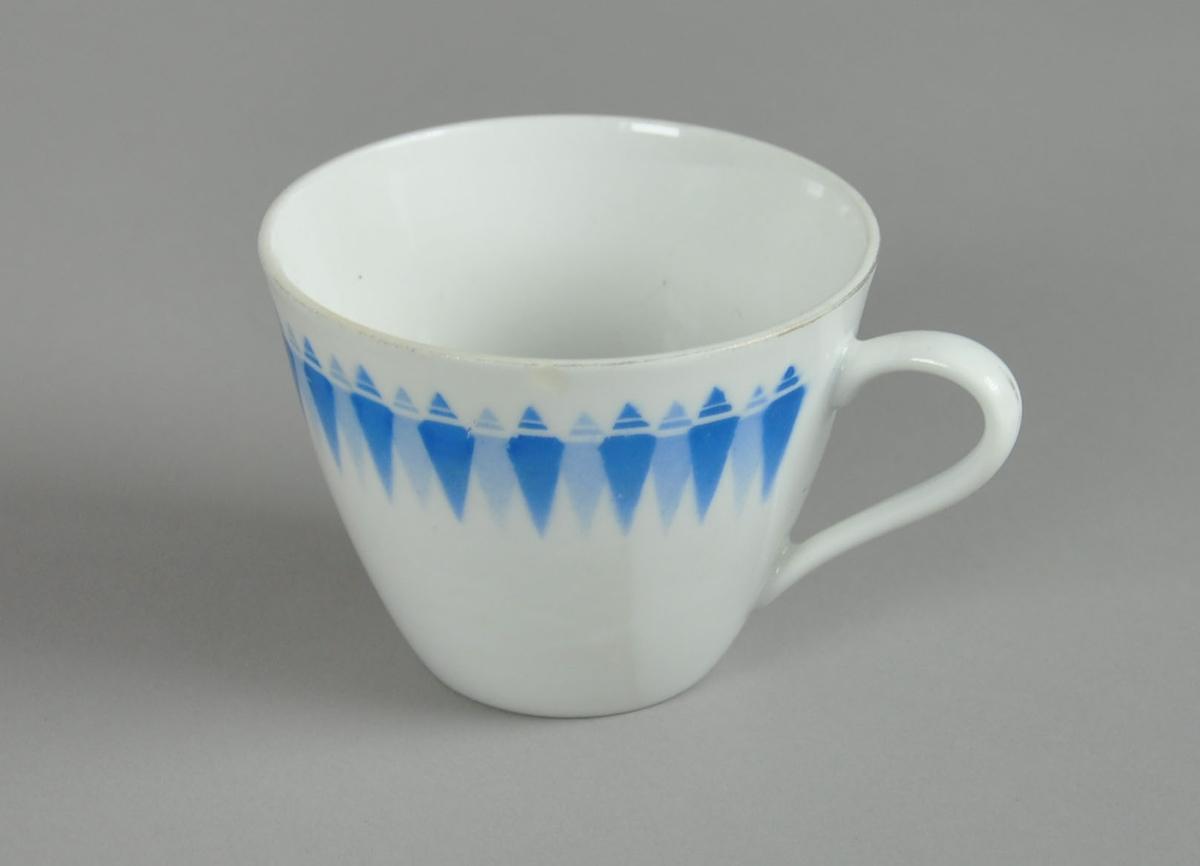 Kopp til servise, av glassert keramikk. På koppen er det malt dekor med motiv av blå romber på rekke.