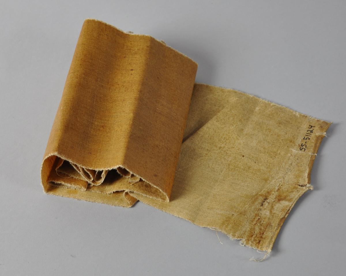 Rems med brunt stoff til hatt. Stoffet bærer preg av bretting og bøying. Ser ut som filt med lakkering på den ene flaten.