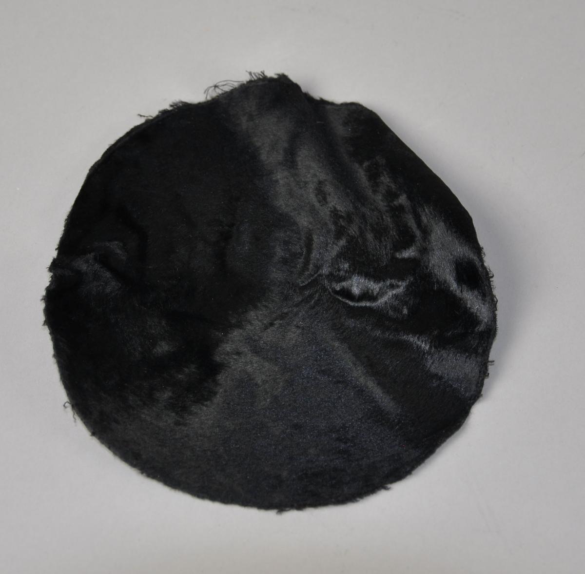 Rundt utsnitt av svart skinn / pels til flosshatt. Utsnittet er til toppen av pullen.