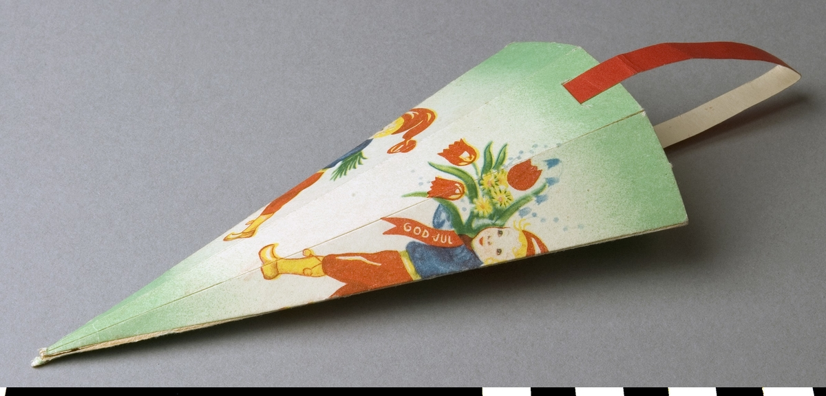 Julgransprydnad, pappersstrut för julgotter. Tryckt motiv med småtomtar bärandes blomsterbukett. Många färger på grön botten och med rött upphängningsband av papp. Struten vikt i sex avsmalnande delar och hoplimmad. Gott skick, endast spetsen litet stött.  Funktion: Dekoration i julgran