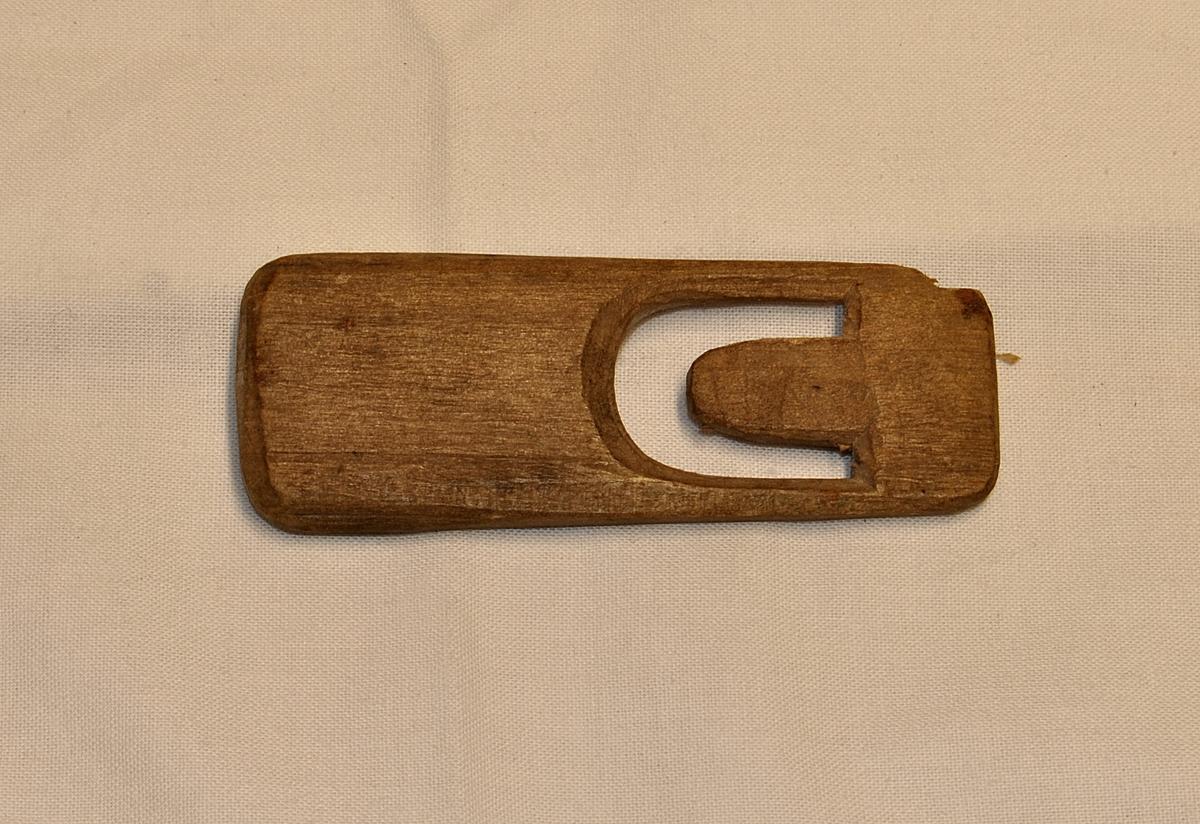 Rektangulær form, heilt flat med ovale hjørner. Det er skore ut ein U figur i eine enden. Lett materiale. Det er skore eit spor i enden over figuren U. Brukt til å binde garn. Dette er den største av dei to nålene.