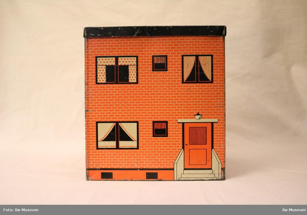 Dekoren gjer at boksen ser ut som ein funkisvilla med mursteinsvegg, inngangsdør og vindauge med gardiner og potteplanter.