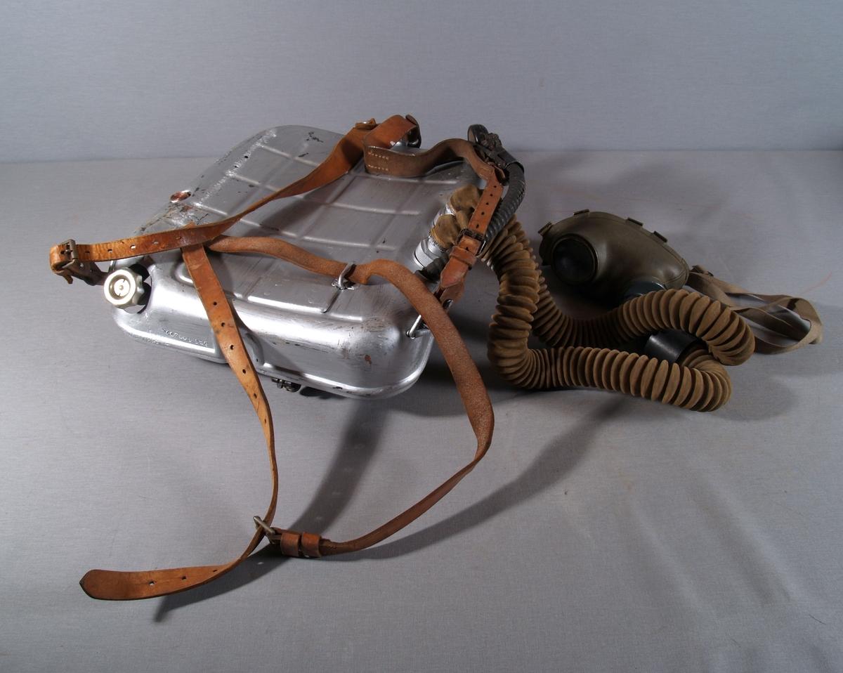 Bærbart gassbeskyttelsesapparat, består av en metallbeholder med ryggseler og magesele i lær. På den ene selen feste for manometer med slange fra beholderen. Beholderen har løst lokk hengslllelt i toppen og festet med tekstilreim. Inni beholderen er det festet surstoffpatron og plass for Kalipatron. Kobling fra patronene til slange og pustemaske på utsiden. Koblingene har regueringsmulighet.
