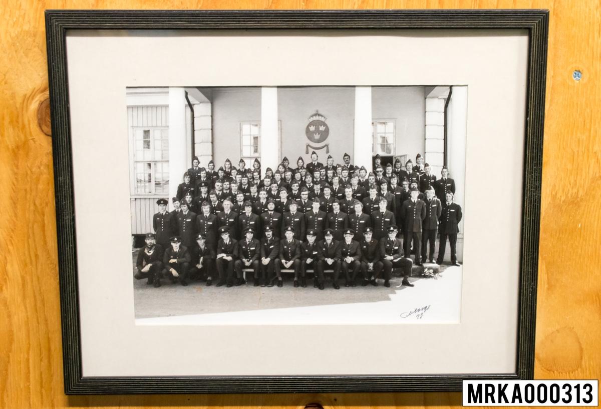 Fotografi taget på befäl och soldater som genomfört grundläggande soldatutbildning på 1:a Batteriet KA 2. Fotografiet taget utanför gymnastikhallen på Gräsvik KA 2. Flobergs Foto.