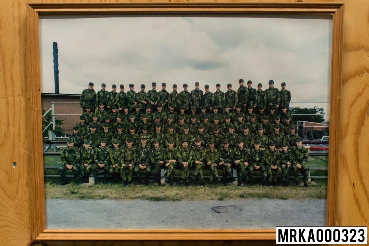 Fotografi taget på befäl och soldater som genomfört grundläggande soldatutbildning på 1:a Batteriet KA 2. Fotografiet taget vid fotbollsplan Rosenholm KA 2.