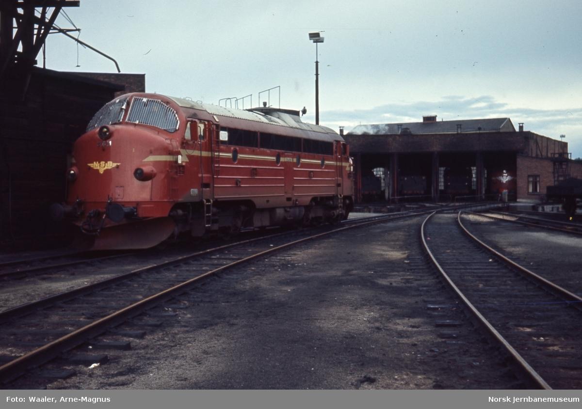 Diesellokomotiv Di 3 611 med lokomotivstallen på Hamar stasjon i bakgrunnen