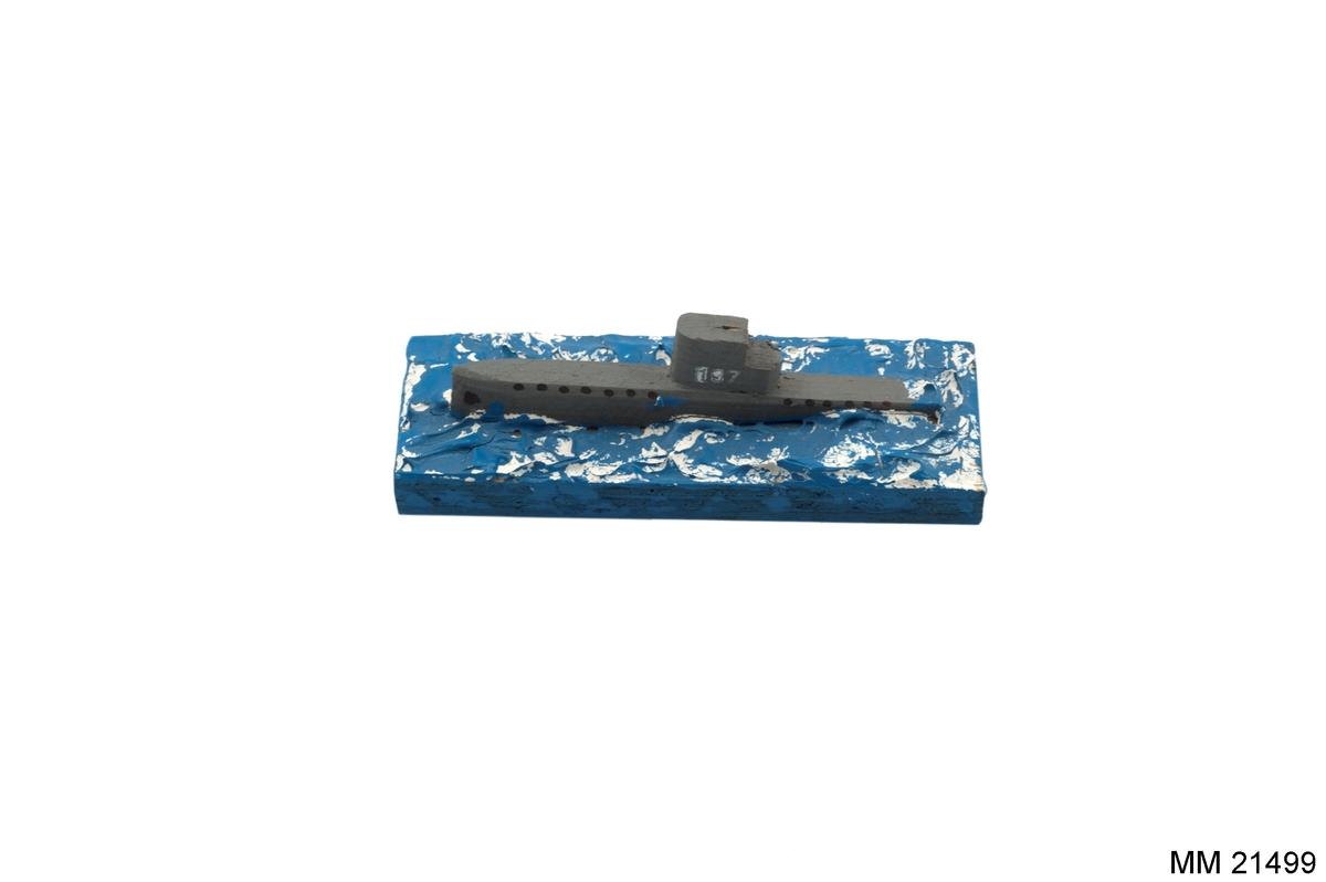"""Ubåt på grund, tillverkad av trä, bestående av rektangulär platta, målad i blått med modellerade vågor. Ubåten i grått märkt: """"137"""" på tornet. Papper på sidan av plattan: """"KARLSKRONA"""". Under platta text: """"Aage Mazetti, Sturkö. Familjetillverkning""""."""
