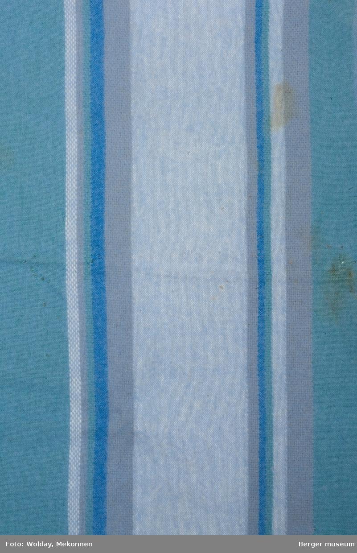 En pleddprøve i stripemønster. Prøven har frynsekant på ene kortside, de resterende tre har klippete sider. Mønsteret karakterisereres av 14 langsgående felt og striper i forskjellge farger, hvorav et gråblått felt litt forskjøvet for midten som flankeres av smalere felt i mørkere grått, blått og grønt. fargene i duse grønn- og blåtoner. Noe møllhull.