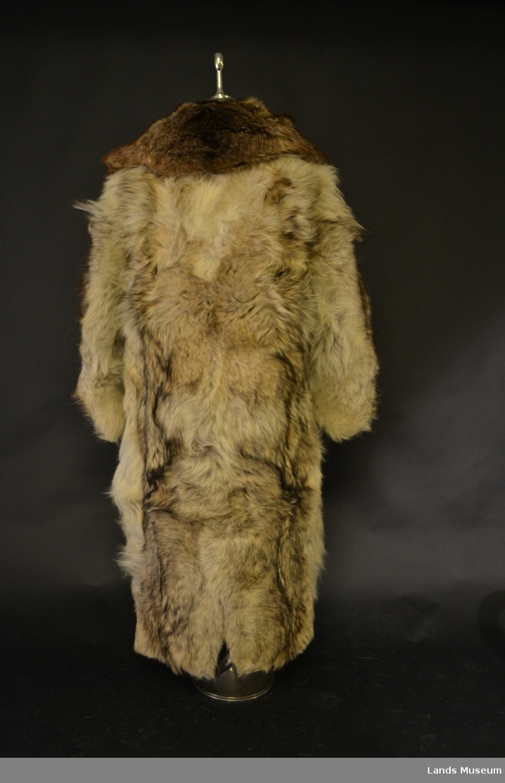 Kjørefrakk i ulvepels med krage i reveskinn. Beige for i kypertvevd ullstoff. To lommer på venstre side. Knapper i skinn.  Merke på innsiden, svart med broderi i gult: AL