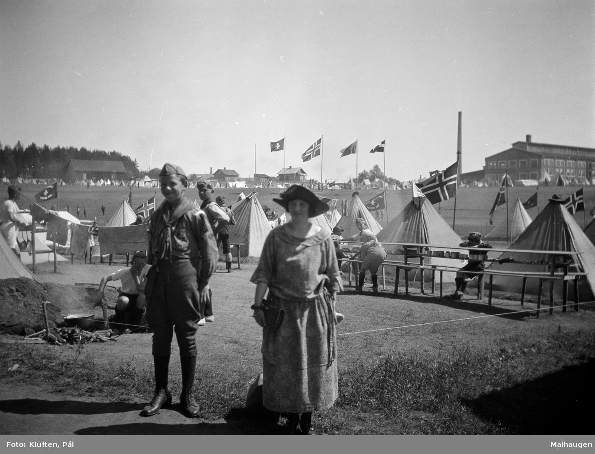 Speiderlandsleir på Hamar 1924. Gutt i speideruniform og kvinne ved teltleiren. Hamar Staalverk i bakgrunn.