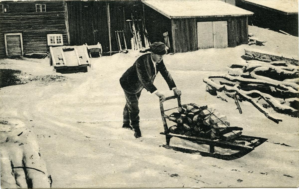 Postkort. Jule- og nyttårshilsen. Fotografisk motiv. Vintermotiv fra et gårdstun. En mann frakter ved på en kjelke. Poststemplet 23.12.1909.