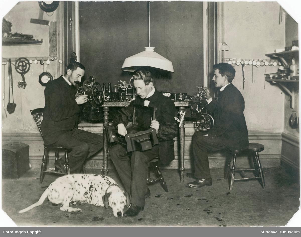 Interiör från urmakeriet på L. Björnströms Optiska Handel senare kallad Björnströms Ur & Optik på Storgatan 17. I mitten ses Ernst Björnström med två anställda urmakare i arbete.