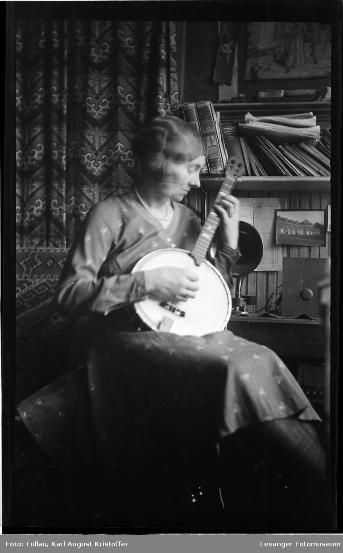 Jenny spiller banjo, foran radioen.