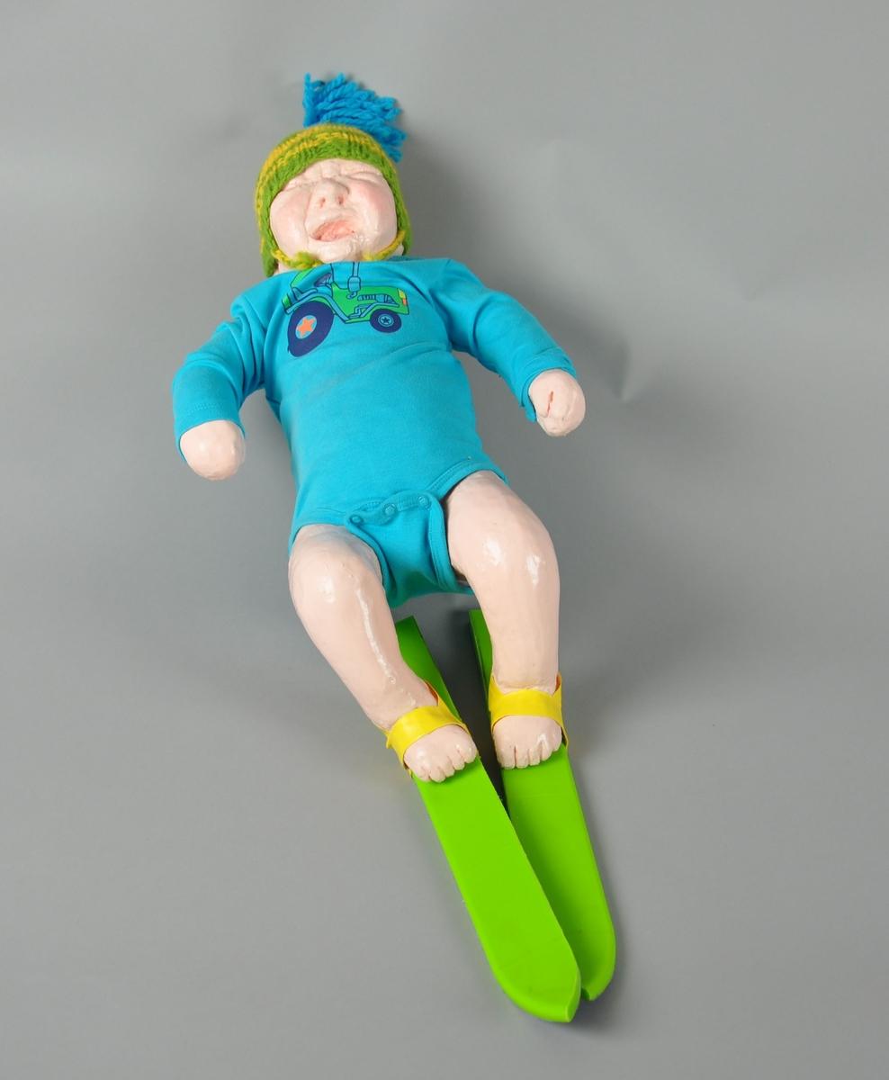 """Dukke med ski på beina. Dukken har på seg en grønn og gul strikket topplue med blå dusk og en blå body med """"Moods of Norway""""-traktor. Skiene er grønne med gule bindinger av tape.  Dukken kan være inspirert av statuen """"Sinnataggen"""" i Vigelandsparken."""