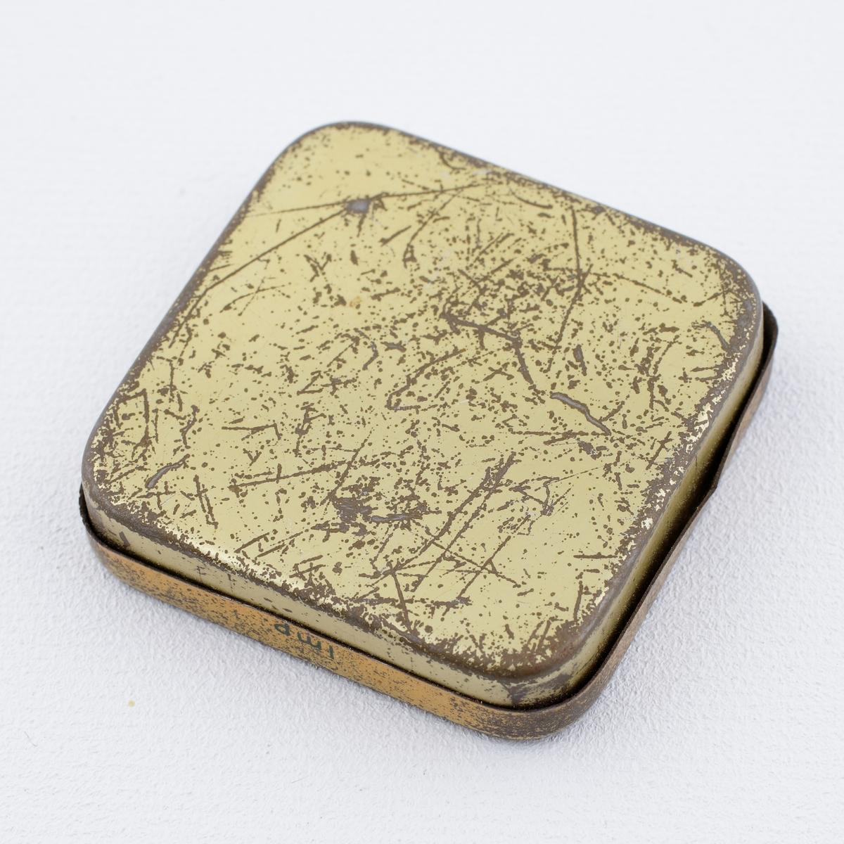 """Ask av plåt. Fyrkantig modell med avrundade hörn och dekor i gult och mörkgrönt. Förvaringsask för grammofonnålar.  Text på locket: """"Ramona Salong guld""""."""